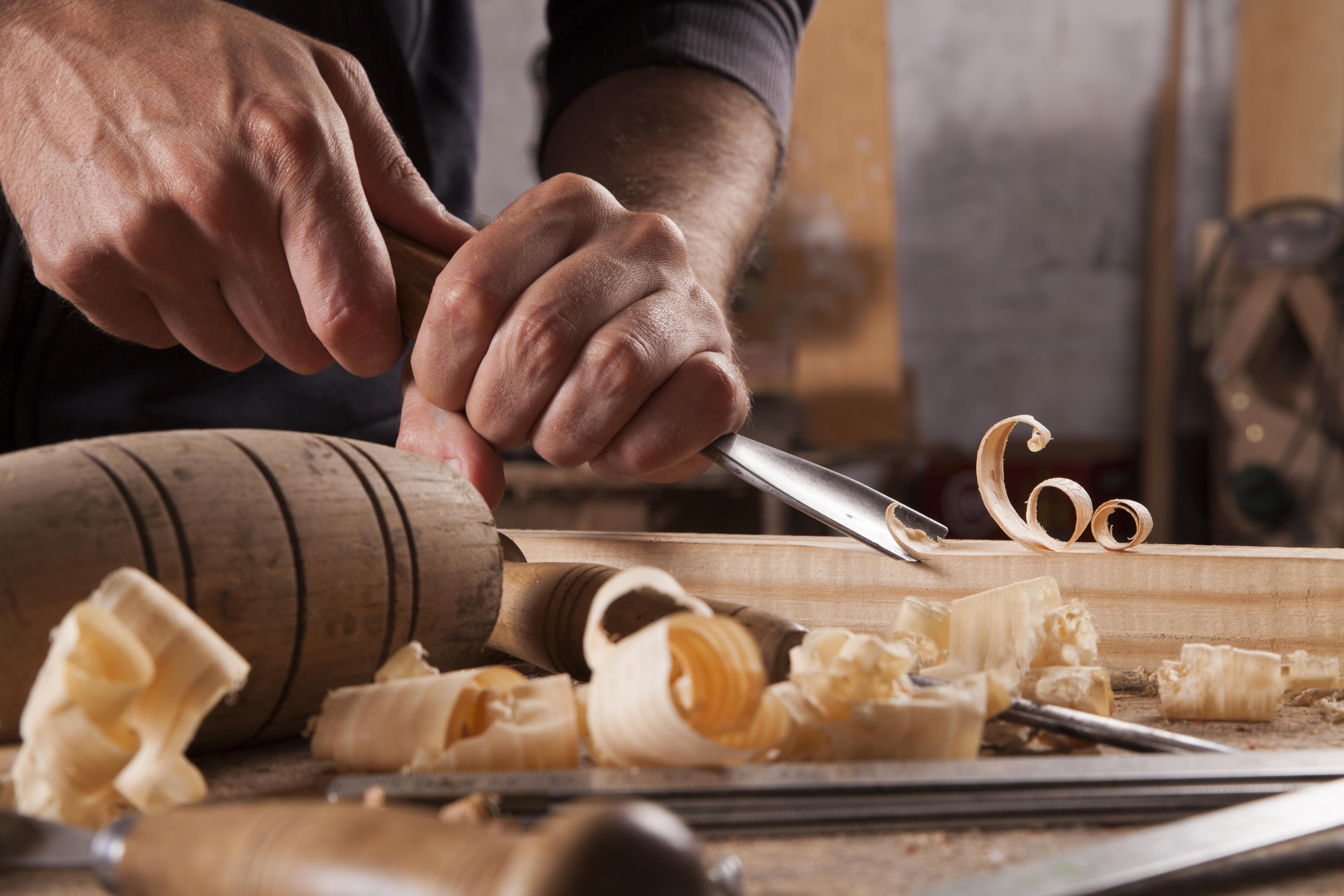 Homme tenant en main un outil pour travailler du bois